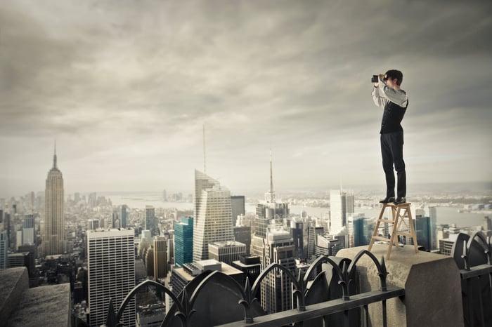 Man standing on step stool on top of skyscraper looking through binoculars