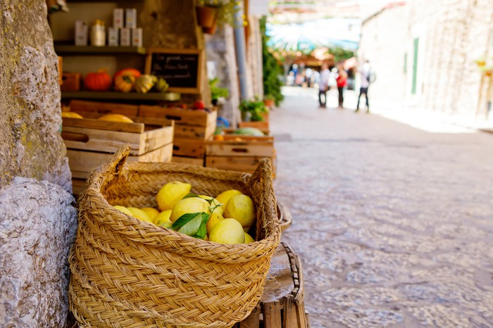 Ripe lemons in a wicker basket for sale in a sunny Italian village.