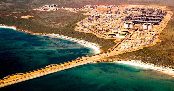 Overhead shot of operational energy facility in an arid climate along a coastline.