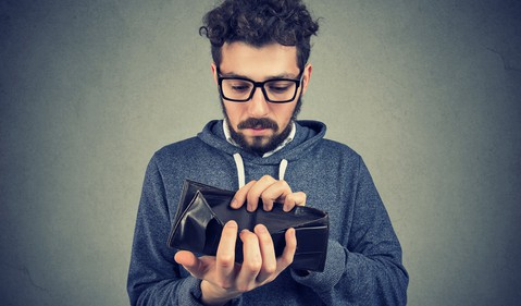 man holding empty wallet open_GettyImages-1002196260