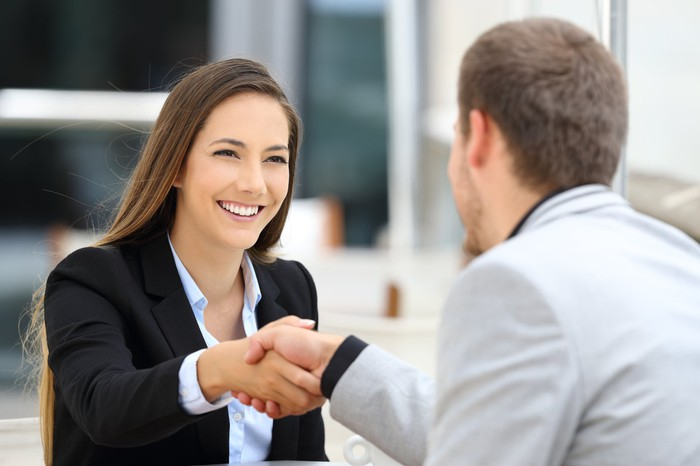 Smiling woman shaking hands with man.