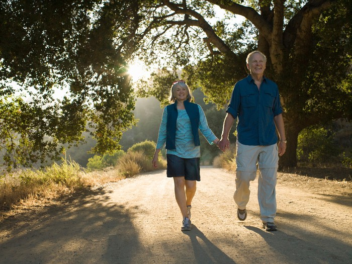 Older man and woman holding hands while walking down a dirt road