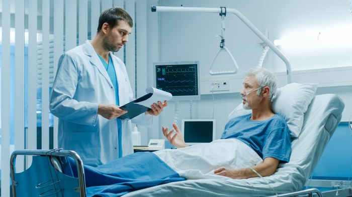 Man in hospital bed talking to doctor standing next to bed