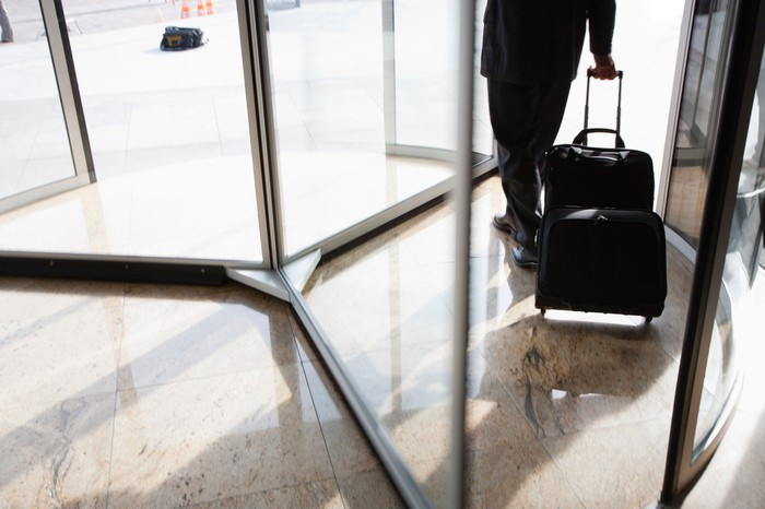 Man walking out of a revolving door, pulling a wheeled bag