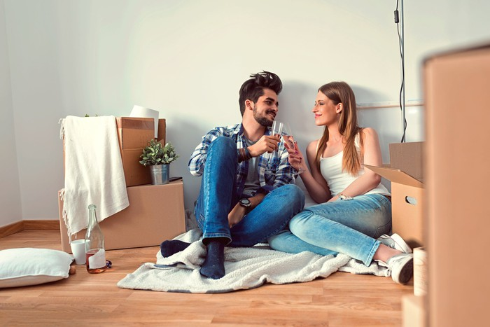 Couple on floor surrounded by moving boxes.