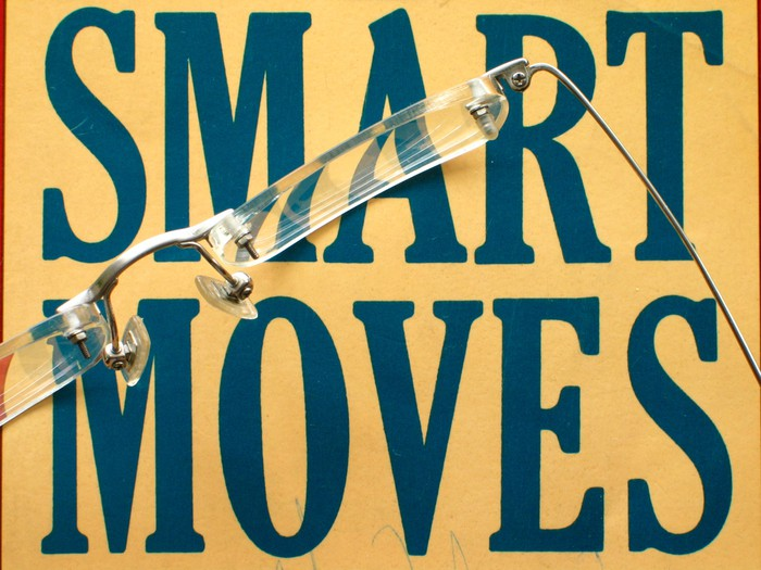 "The words ""SMART MOVES"" printed on a yellow background, with a pair of eyeglasses sitting on top"