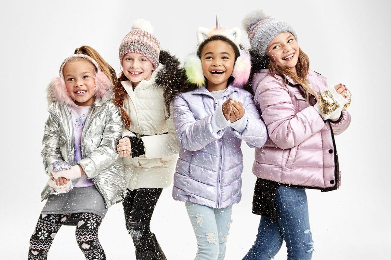Four kids wearing winter jackets.