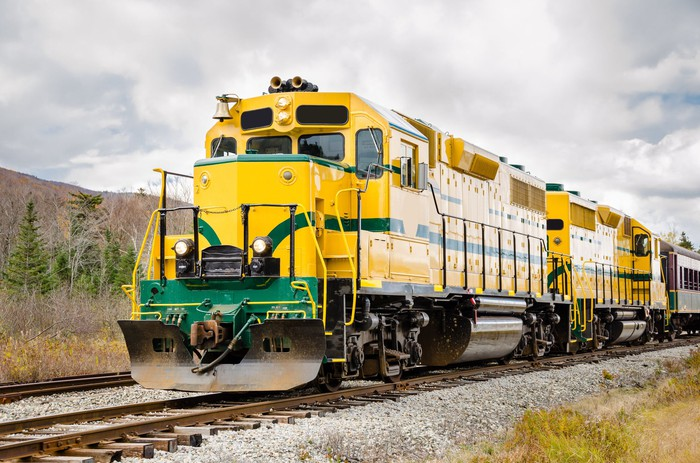 Yellow and green locomotive under a cloudy sky.