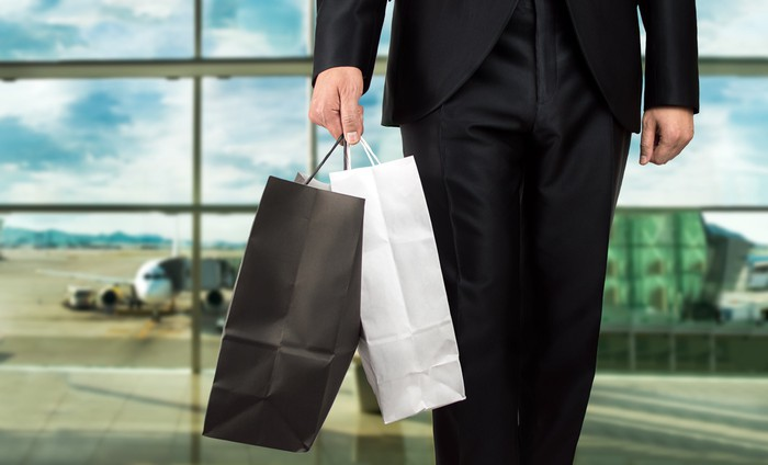 Man holding shopping bags in airport terminal.