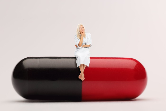 Patient in hospital gown thinking about something while sitting on a giant medicine capsule that's black on the left side and red on the other.