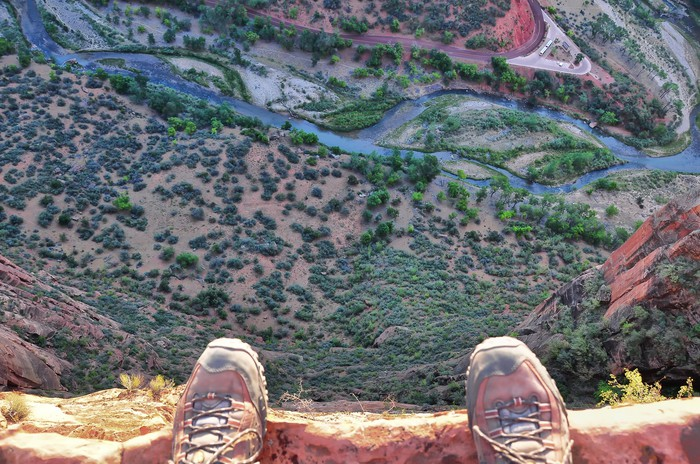 A pair of shoes on the edge of a cliff.