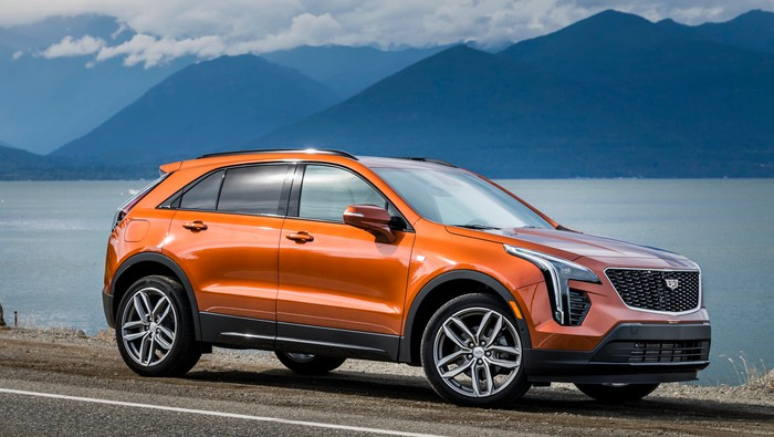 An orange 2019 Cadillac XT4, a compact luxury crossover, parked next to a lake.
