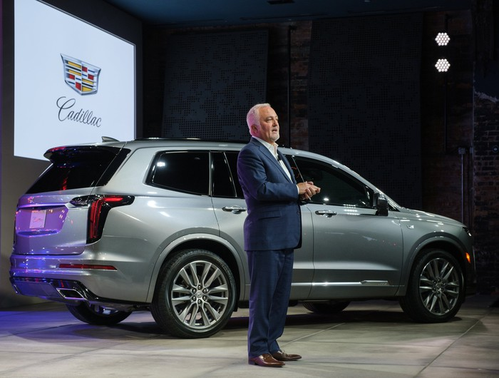 Carlisle is speaking on a stage. Behind him is a silver Cadillac XT6, a midsize luxury crossover SUV.