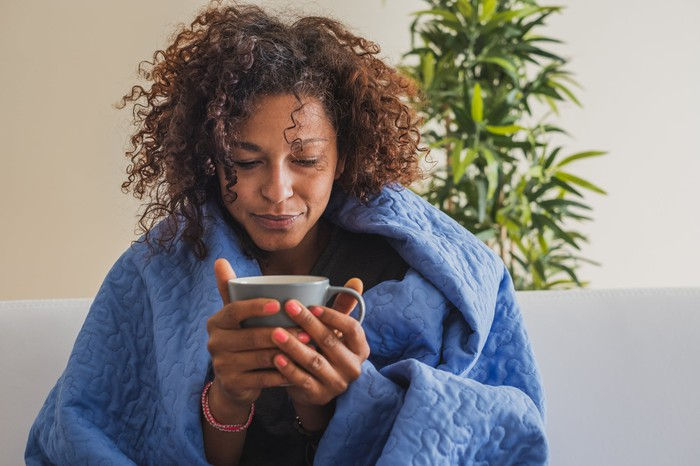 Woman wrapped in blanket holding a mug.