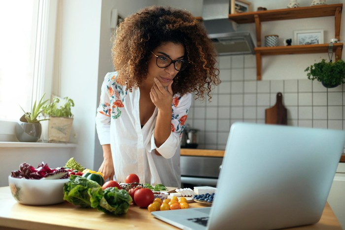 A woman looks at a computer while she cooks.
