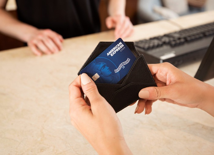 Female hands pulling an American Express card from a wallet.