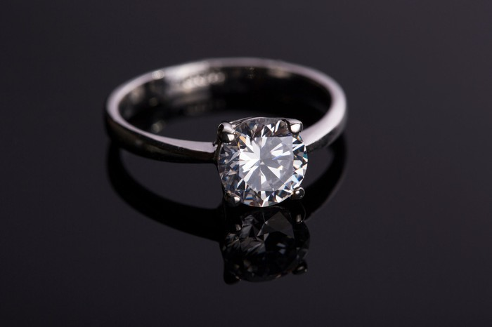 A diamond ring on a black surface