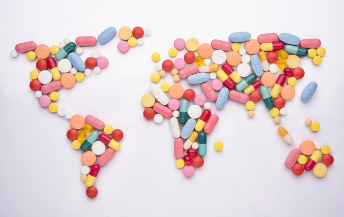 Different pills arranged in shape of world map.