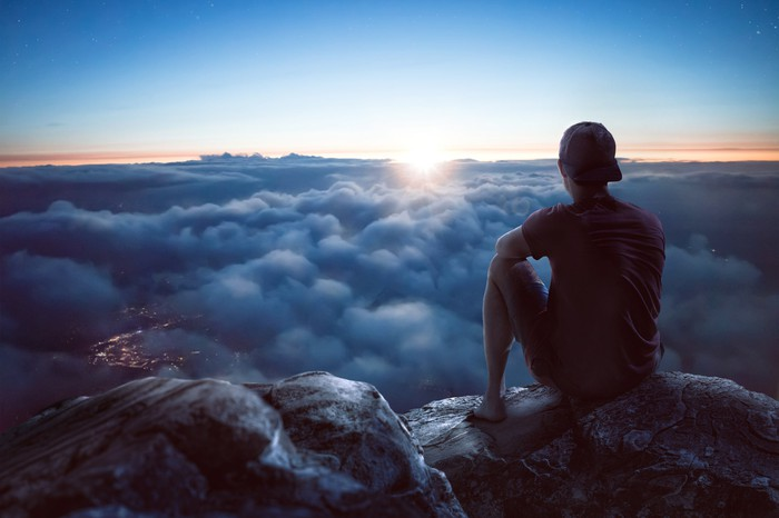 A young man is sitting on a rock on a summit overlooking a vast ocean of clouds.