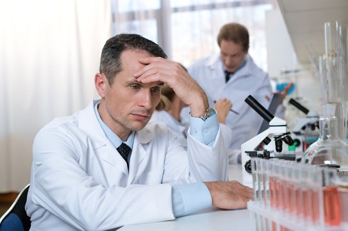 A disheartened-looking man in a lab coat seated at a table with a microscope and test tubes on it.