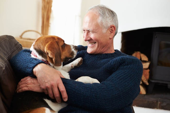 Smiling senior man holding dog.