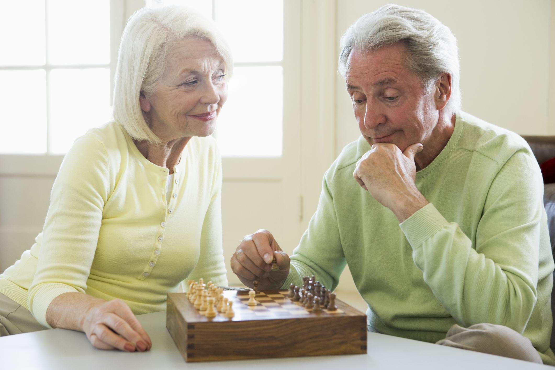 Senior woman and man playing chess