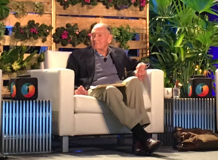 Jack Bogle sitting in a white chair on a stage in front of greenery.