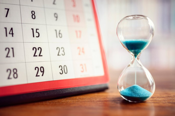 A half-empty hourglass on a wooden table next to a calendar.