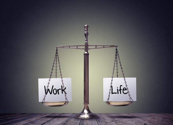 A balance scale carries the words work and life.