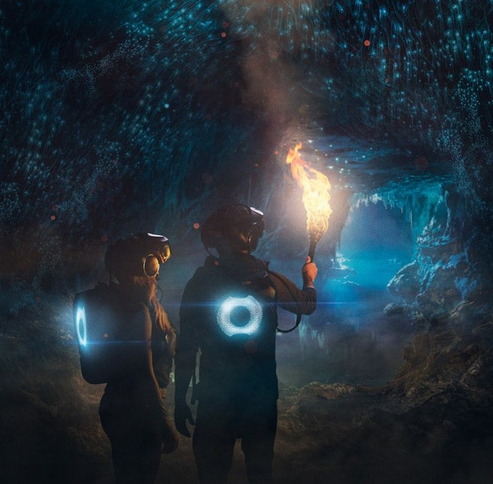 Two people in VR headsets inside a virtual cave created by The Void's VR equipment.