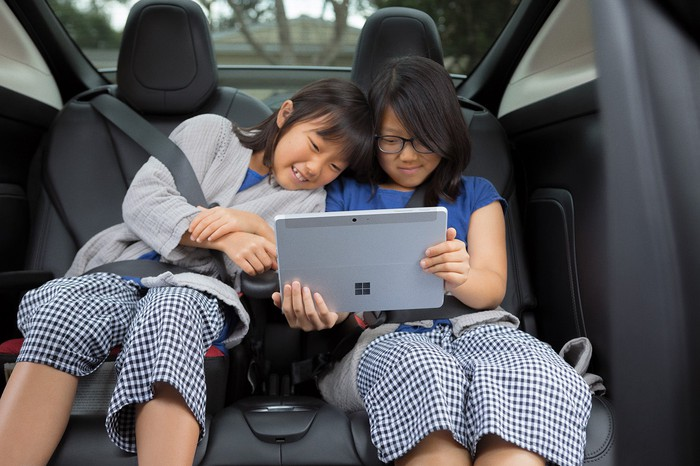 Two children watching a movie on a Microsoft Surface tablet in the back seat of a car.