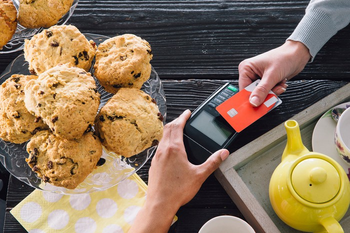 Customer making credit card payment by tapping card on card reader across a table set with muffins and tea.