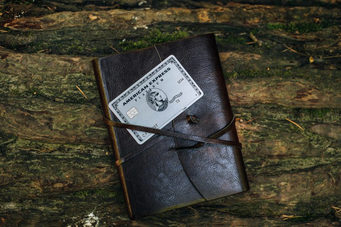 An American Express Platinum card sitting on top of a leather folio