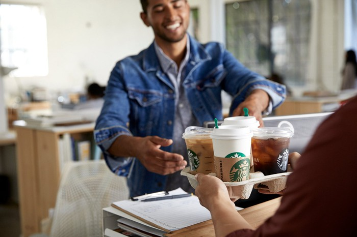 A person accepts a Starbucks delivery order.