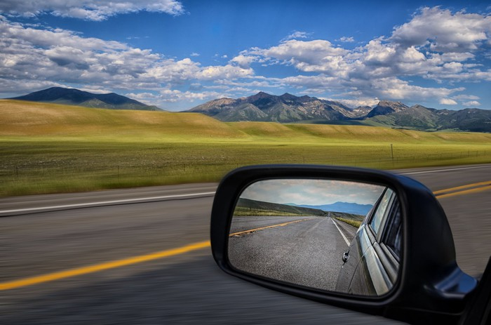 A rearview mirror reflecting a highway with mountains in the distance