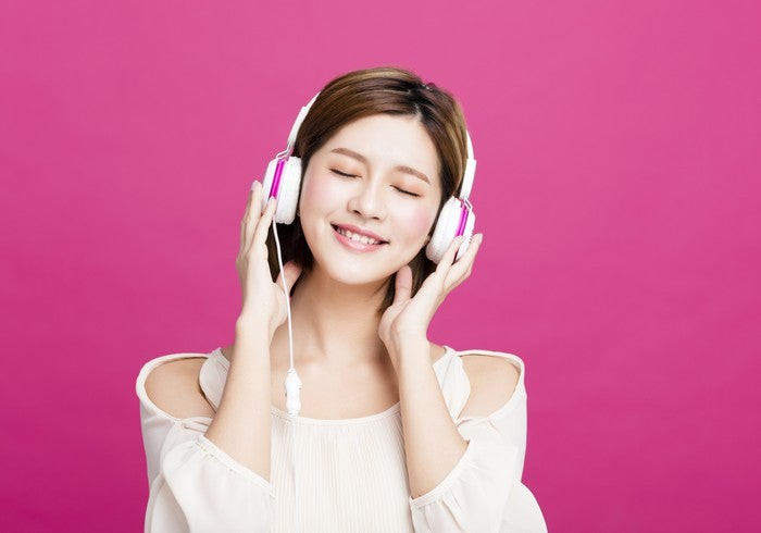 A young woman listening to music on white-and-pink headphones.