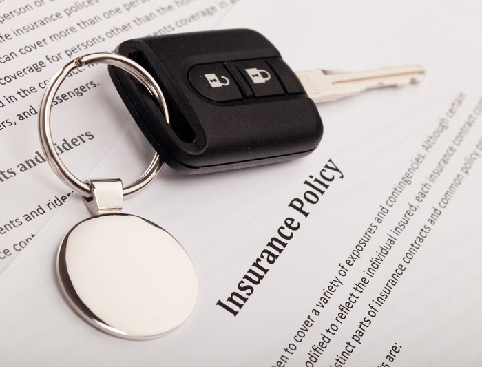 Keys sit on top of an insurance policy.