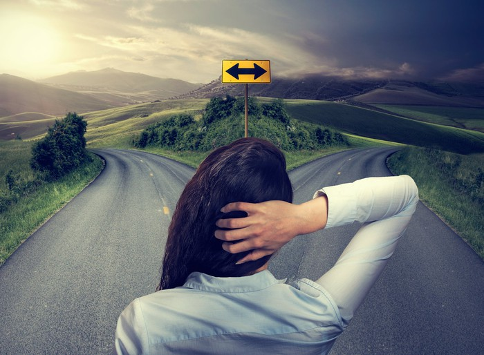 A woman looks at two roads forking in different directions in a mountainous countryside.