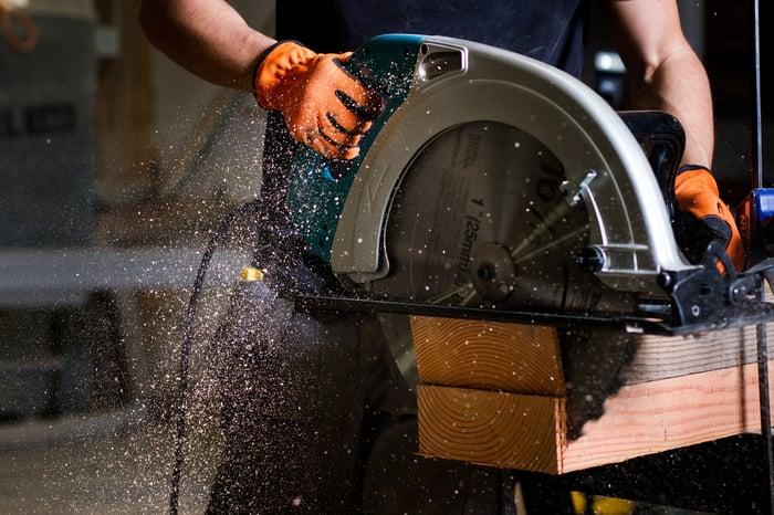 Man using large saw.