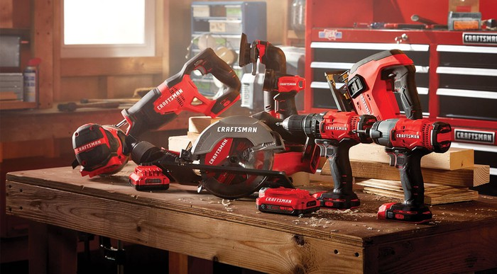 An assortment of Stanley Black & Decker's Craftsman-branded tools on a wood table in a workshop.