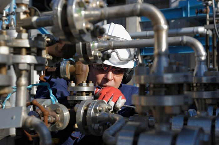 Oil services worker inspecting valves.