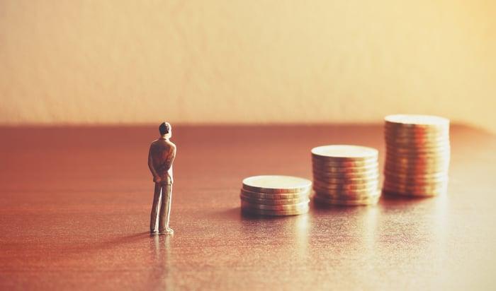 Miniature person watching savings grow