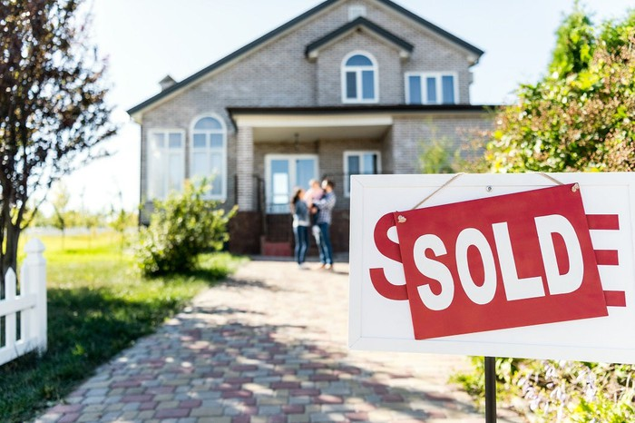 """Photo of a """"sold"""" sign in front of a suburban home."""