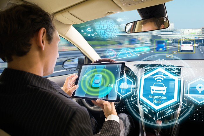 Man on a smart tablet in an autonomous driving vehicle