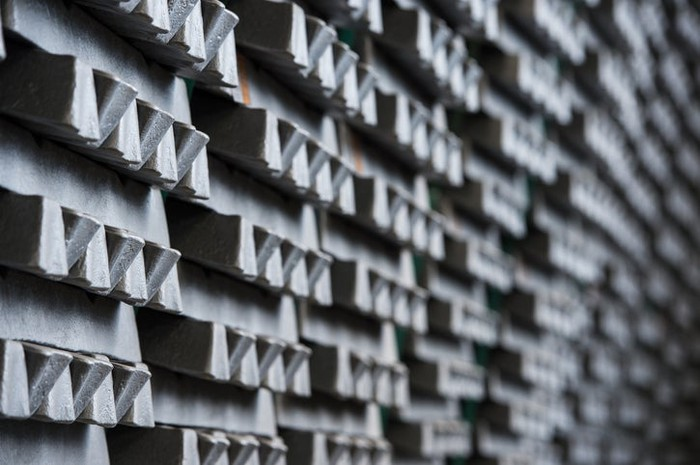 Aluminum ingots stacked in a warehouse.
