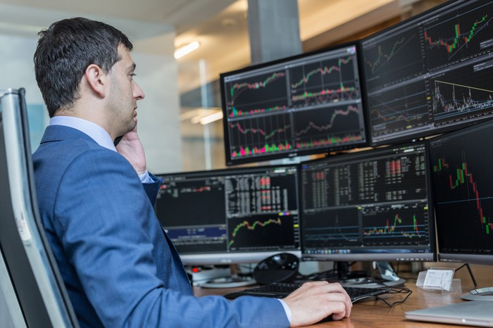 Stock trader sitting at a desk. with computer screens all around him.