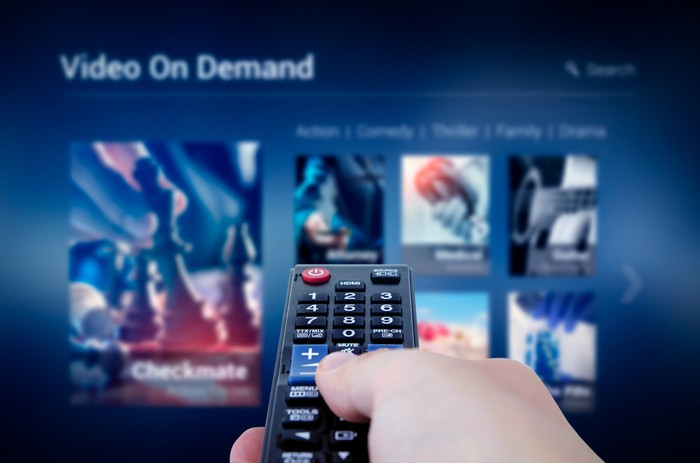 A hand holding a remote control pointed at a screen displaying streaming video titles.
