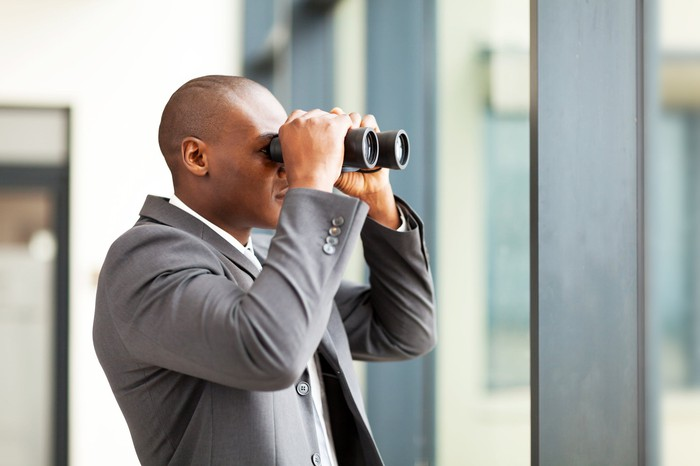 A bald businessman looking out a window with binoculars.