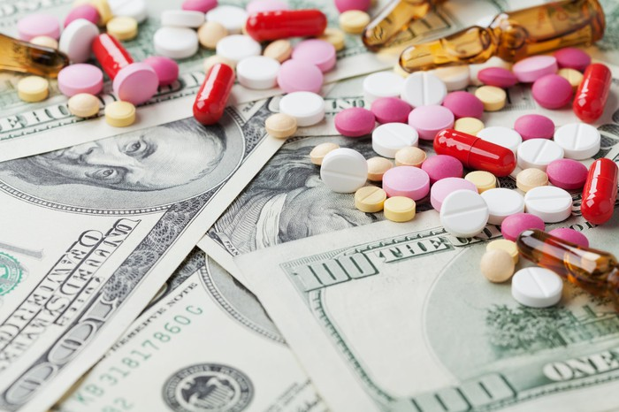 Colorful assortment of pills on a bed of hundred dollar bills.