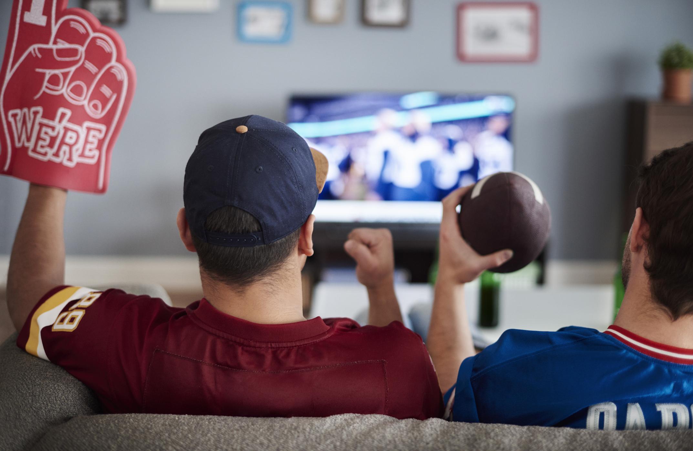 Two men watch football on TV.